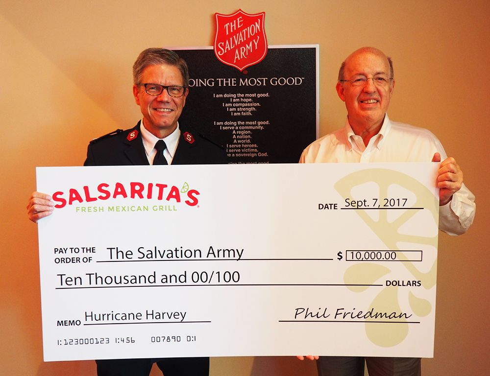 Salsarita's Fresh Mexican Grill CEO Phil Friedman presents one check to Major Larry Broome with the Charlotte Salvation Army.