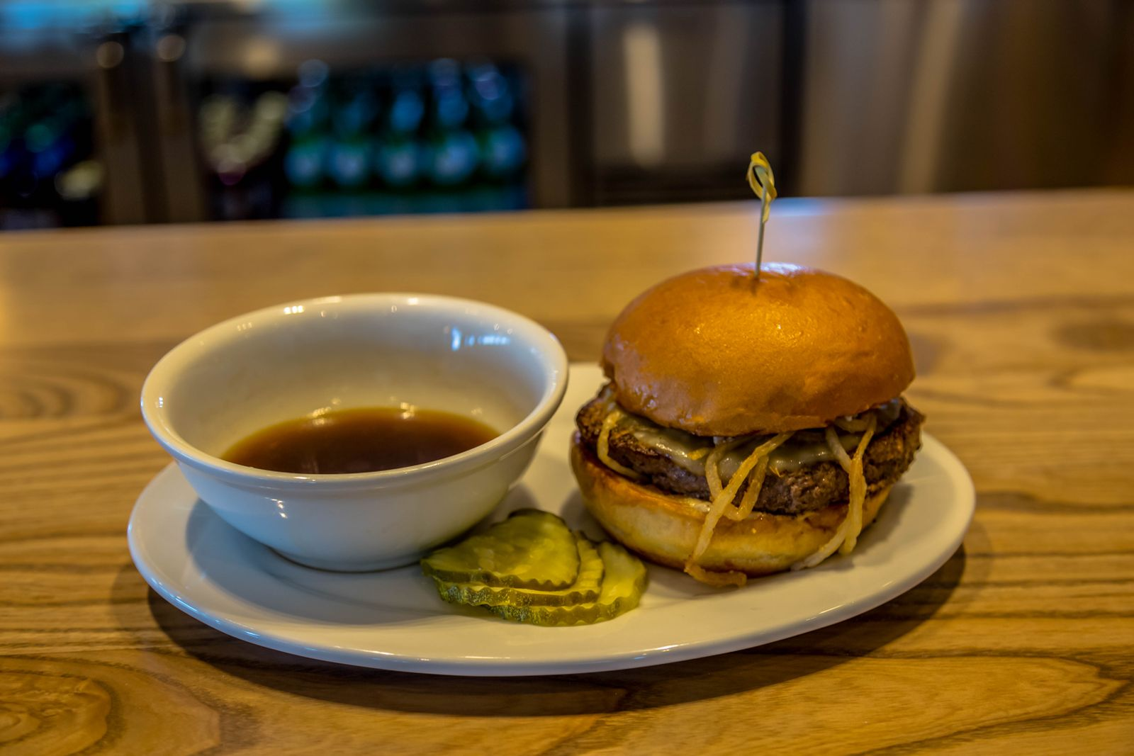 The Prime Rib Burger is a Certified Angus Beef & Prime Rib Blended Patty, Provolone Cheese, Fried Onion Strings, Parmesan Horseradish Créme & served with Aus Jus.