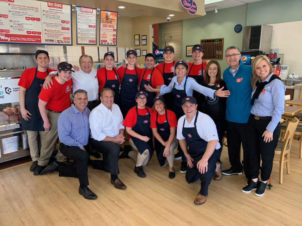 Jersey Mike's Founder & CEO Peter Cancro (kneeling, 2nd from left) celebrated the company's 9th Annual Day of Giving in Northridge, Calif., with Craig Pollard (standing second from right), founder of Cancer for College, and Jersey Mike's local owners, area directors, and team members.