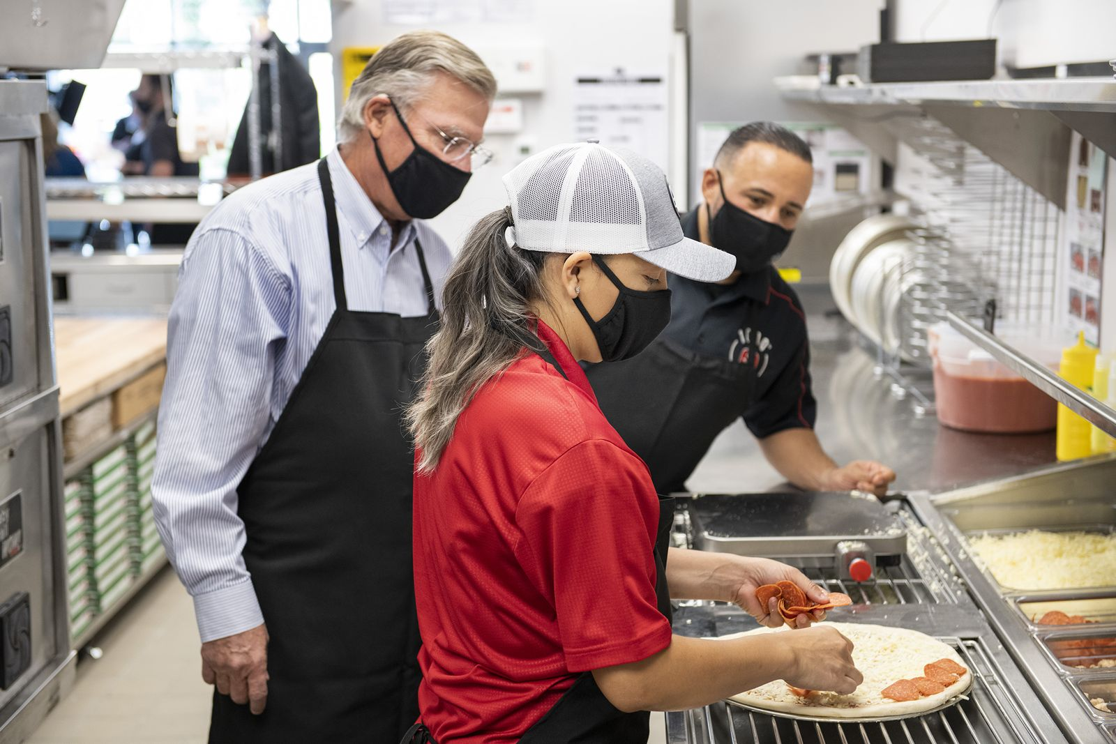 Marco's Pizza CEO Jack Butorac, left, and franchisee Rafi Vargas, right,  look on as franchisee Kattya Barbaran prepares a pizza, Tuesday, October 20, 2020, in Kissimmee, Fla. Vargas and Barbaran are owners of Marco's Pizza's 1000th store and are residents of Kissimmee.