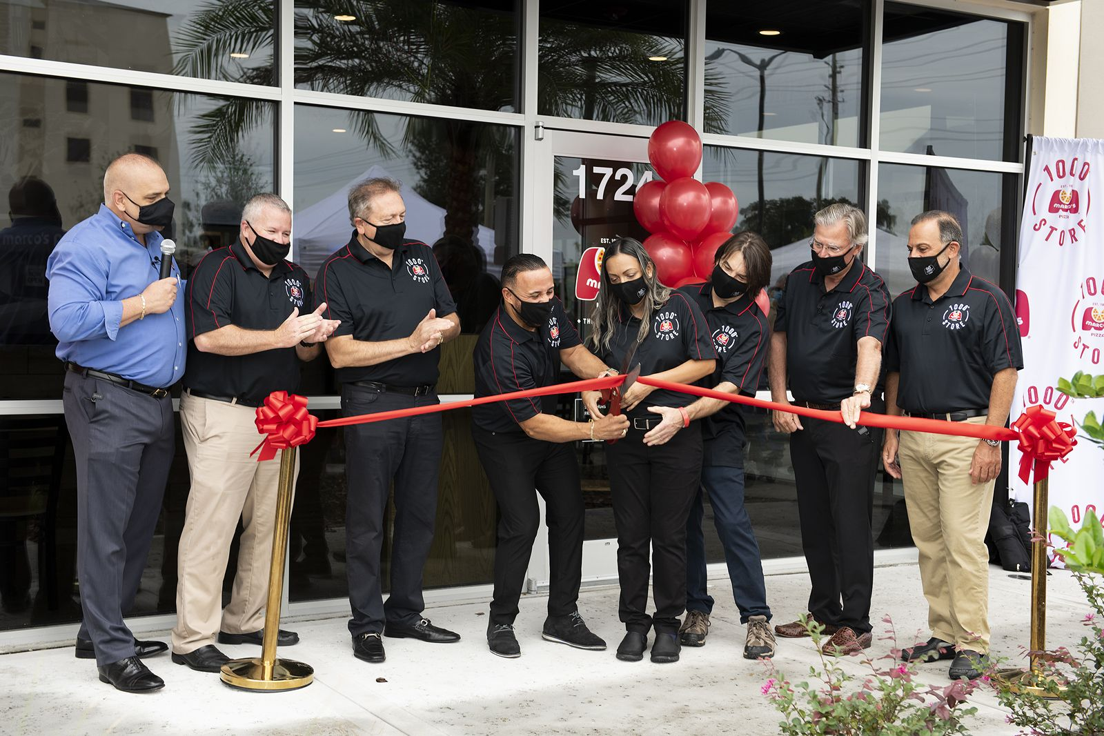 Marco's Pizza franchisees Rafi Vargas, Kattya Barbaran, and Ed Boyer (all holding scissors, center) cut a Grand Opening ribbon at the brand's 1,000th store in Kissimmee, Fla. on Wednesday, Oct. 21, 2020. The three are residents of Kissimmee. Flanking them, from left, are Tony Libardi, Marco's President and COO, Mike Fletcher, Marco's Area Representative, founder Pasquale Giammarco, Marco's Pizza CEO Jack Butorac, and Glenn Ajmo, Marco's Pizza Area Representative.